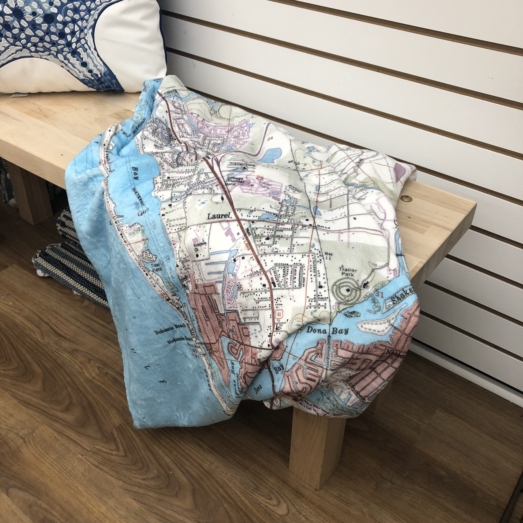blanket with map of Venice Florida lying on on bench